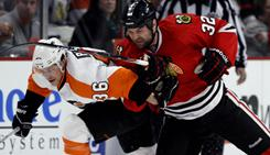 The Philadelphia Flyers' Darroll Powe, left, and Chicago Blackhawks' John Scott go after a loose puck during the first period Sunday.