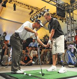 PGA pro Jim Estes, left, conducts a clinic as part of the Wounded Warriors program at the 90th PGA Championship at Oakland Hills Country Club in Bloomfield Township, Mich. Estes works here with Army veteran Ben Dellinger.