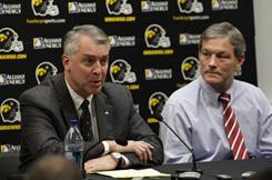 Iowa athletics director Gary Barta, left, speaks at a press conference in December as football coach Kirk Ferentz, right, looks on. Barta said in a statement on Tuesday that the school's next step is to figure out what made the football players ill so it can be avoided in the future.