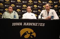 Iowa Dr. John Stokes, right, speaks about the medical condition affecting 13 Iowa football players during a news conference with Biff Poggi, left, father of freshman linebacker Jim Poggi, one of the affected players, and Director of Football Operations Paul Federici (center) on Wednesday.