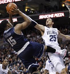 Georgetown's Austin Freeman shoots over the defense of Villanova's Maurice Sutton.