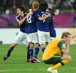 Australia defender David Carney, kneeling in front, reacts as Japan's players celebrate winning the 2011 Asian Cup on Saturday.
