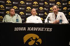 University of Iowa Dr. John Stokes, right, Biff Poggi, left, and Iowa director of football operations Paul Federici speaks about the medical condition affecting 13 Iowa football players.