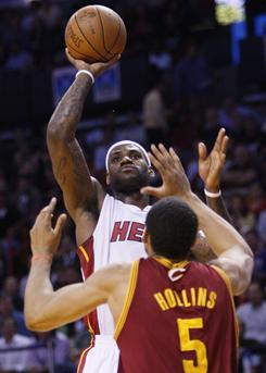 Miami's LeBron James goes up for a shot against Cleveland's Ryan Hollins (5) during their matchup Monday night. James scored 24 in the win.