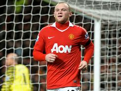 In English Premier League action, Machester United's Wayne Rooney celebrates scoring his second goal of the match against Aston Villa.