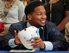 First Coast High School football player Eric Beverly smiles as he holds a Florida State cap after signing his letter of intent to play for the Seminoles.