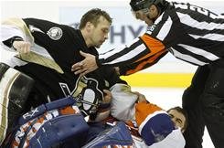 Pittsburgh goalie Brent Johnson, left, is restrained by referee Rob Martell as he fights New York Islanders goalie Rick DiPietro late in the third period on Wednesday.