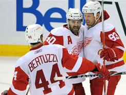 Detroit's Todd Bertuzzi (44) and Henrik Zetterberg (40) congratulate Johan Franzen (93) after Franzen scored his fifth goal in the team's 7-5 win over Ottawa.
