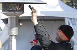 Michael Maness, the caddie for Bill Haas, warms up the grips for Haas at a propane heater during a lengthy frost delay prior to the first round of the Waste Management Phoenix Open on Thursday in Scottsdale, Ariz.