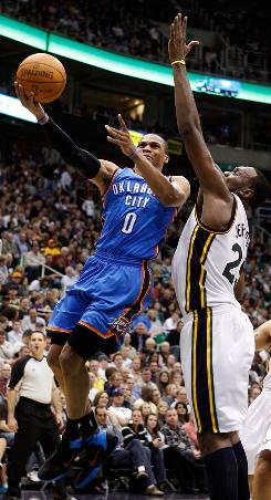 Oklahoma City's Russell Westbrook gets by Utah's Al Jefferson for a shot on Saturday. Westbrook finished with 33 points and the Thunder beat the Jazz 121-105.
