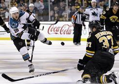 San Jose's Devin Setoguchi (16) shoots and scores into an empty net as Boston's Patrice Bergeron (37) tries to defend the play. The Sharks won 2-0.