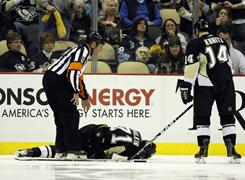 The Penguins' Evgeni Malkin lies injured on the ice during Friday's game vs. the Sabres in Pittsburgh. Malkin tore two ligaments in his right knee.