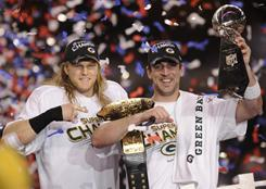 Packers quarterback and Super Bowl XLV MVP Aaron Rodgers holds the Lombardi Trophy as linebacker Clay Matthews puts a championship belt on his shoulder.