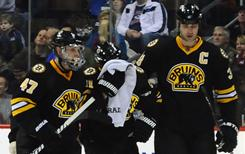 Boston Bruins center Marc Savard, center, is helped off the ice by defenseman Zdeno Chara, right, and defenseman Steve Kampfer after Savard was checked into the boards.
