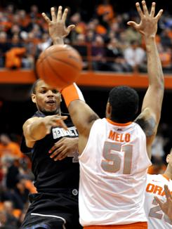 Georgetown's Chris Wright, left, passes around Syracuse's Fab Melo during the first half of their game in Syracuse, N.Y., on Wednesday.