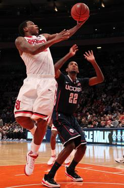 St. John's guard Dwight Hardy, left, drives to the net as Connecticut's forward Roscoe Smith defends during the first half at Madison Square Garden.