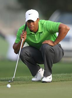 Tiger Woods lines up a putt on his way to a 6-under 66 during the second round of the Dubai Desert Classic on Friday.