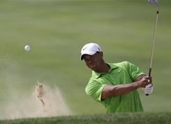 Tiger Woods fires a bunker shot during Round 2 of Dubai Desert Classic in the United Arab Emirates. The superstar shot 66 and trails by four strokes.