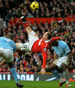 Manchester United's Wayne Rooney, wearing the red jersey, scores the team's second goal during the Saturday's maych against Manchester City at Old Trafford.
