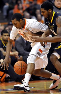 Syracuse's Kris Joseph, left, battles West Virginia's John Flowers for a loose ball during their game in Syracuse, N.Y.