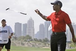 Tiger Woods tosses his putter to caddie Steve Williams during the final round of Dubai Desert Classic on Sunday. Woods struggled to a 75, falling out of contention.