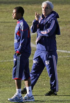 Former France captain Patrice Evra, left, led a players' revolt against coach Raymond Domenech, right, at the World Cup last summer.