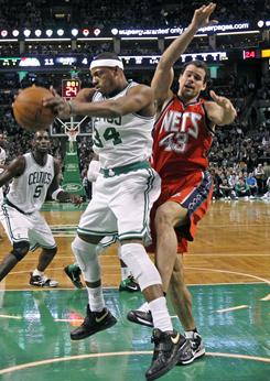 Celtics forward Paul Pierce, left, grabs a rebound against Nets forward Kris Humphries during the first quarter of their game Wednesday night in Boston.