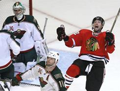 Blackhawks right wing Troy Brouwer, right, celebrates his third-period goal much to the chagrin of Wild goalie Jose Theodore and center John Madden (11) during their game Wednesday. Chicago beat Minnesota 3-1.