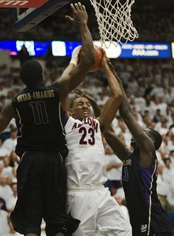 Arizona's Derrick Williams (23) grabs the rebound between Washington's Matthew Bryan-Aamaning (11) and Darnell Gant during Arizona's 87-86 victory on Saturday.