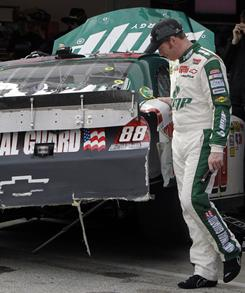 Dale Earnhardt Jr. looks at the damage to his car after he was involved in a crash during practice Wednesday.