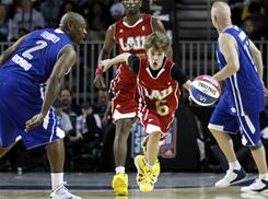 Teen Singing sensation Justin Bieber, center, makes his way down the court during the BBVA All-Star celebrity basketball game Friday at the Staples Center in Los Angeles.