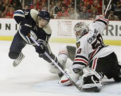 Matt Calvert, left, scores past Corey Crawford to help the Blue Jackets top the Blackhawks.
