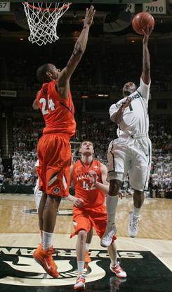 Michigan State's Kalin Lucas (1) puts up a layup against Illinois' Mike Davis (24) and Tyler Griffey (42) during the first half of their game in East Lansing, Mich.