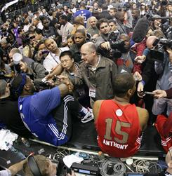 LeBron James, left, and Carmelo Anthony are mobbed after All-Star practice on Saturday. Anthony said the trade talk was taking a toll.