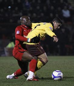 Leyton Orient's Jonathan Tehoue, left, vies with Arsenal's Denilson during their FA Cup match in London on Sunday. The teams tied 1-1 and will play again for the right to play Manchester United.