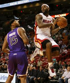 The Heat's LeBron James, right, looks to pass as the Kings' Demarcus Cousins defends during the first quarter of their game Tuesday. James had 31 points despite sitting out the fourth quarter as Miami cruised to 117-97 win against Sacramento.