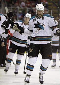 San Jose's Joe Thornton is congratulated by teammates after scoring his 300th career goal during Tuesday's night's game against Detroit. The Sharks beat the Red Wings 4-3.