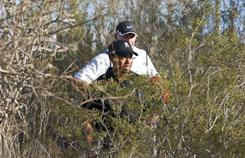 Tiger Woods and caddie Steve Williams look over their troubles after an errant drive landed in the desert waste on No. 1, the first extra hole in Woods' loss to Thomas Bjorn of Denmark on Thursday in the WGC- Accenture Match Play Championship in Marana, Ariz.