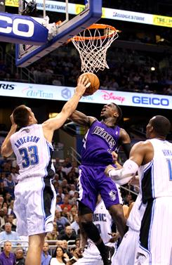 Jermain Taylor of the Kings, center, drives to the basket against the Magic's Ryan Anderson during Sacramento's surprising win in Orlando. Taylor led the Kings with 21 points.