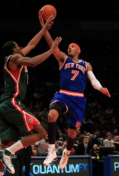 Carmelo Anthony, right, goes up for two points in his Knicks debut Wednesday night vs. the Bucks. Anthony led New York's win with 27 points.