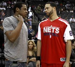 New Jersey Nets point guard Deron Williams talks with Jay-Z as Beyonce Knowles, center, is seen courtside prior to the start of Williams' Nets home debut. Williams finished with 13 points and 18 assists in the losing effort.