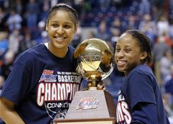 Connecticut Huskies forward Maya Moore, left, and guard Lorin Dixon hold up the Big East regular-season championship trophy after their 82-47 win over Syracuse.