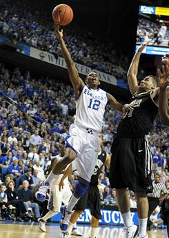 Kentucky's Brandon Knight (12) shoots while being defended by Vanderbilt's Jeffery Taylor (44) Tuesday. Knight scored 17 points in the Wildcats' 68-66 win.