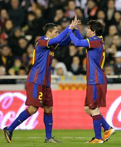 Barcelona's Argentinian forward Lionel Messi, right, celebrates with Barcelona's Brazilian defender Adriano after scoring during the Spanish league football match opposing Valencia and Barcelona at Mestalla stadium on Wednesday night in Valencia.