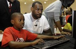 Heat forward LeBron James, right, sits with Cam'ron Lightbourne, 8, at a new computer during a charity event at the Northwest Boys & Girls Club in Miami.