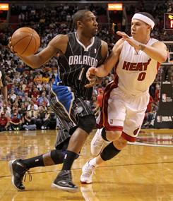 The Magic's Gilbert Arenas drives against the newest member of the Heat, Mike Bibby, in Thursday's game in Miami. Arenas scored 11 points off the bench, including three of club's 11 three-pointers, as Orlando rallied from a 24-point deficit for the win.