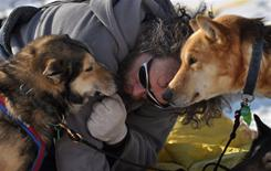 Sebastian Schnuelle visits with his dogs Scruggs, Grisman and Cougar at the Takotna, Alaska, checkpoint on March 10, 2010, during the Iditarod Trail Sled Dog Race.