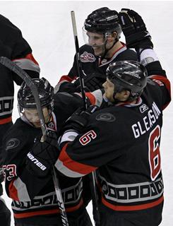 Jamie McBain, top, celebrates his game-winning, overtime goal with his teammates as the Hurricanes downed the Sabres in Carolina.