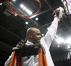 Missouri State head coach Cuonzo Martin displays the remains of the net after he cut the last piece after the Bears defeated Wichita State to clinch the Missouri Valley Conference title.