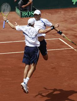 The USA's Mike Bryan, back to camera, and Bob Bryan celebrate their victory Saturday against Nicolas Massu and Jorge Aguilar of Chile in a Davis Cup tie in Santiago, Chile.